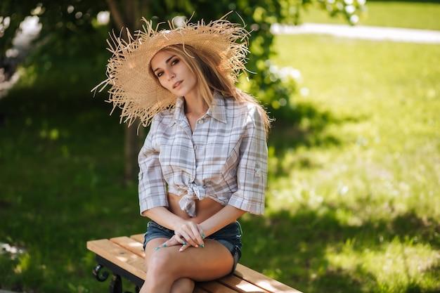 麦わら帽子とショートパンツの女性が公園のベンチに座っています