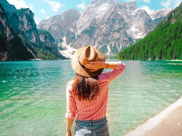Женщина в полосатой рубашке держит шляпу в горах возле озера брис в италии