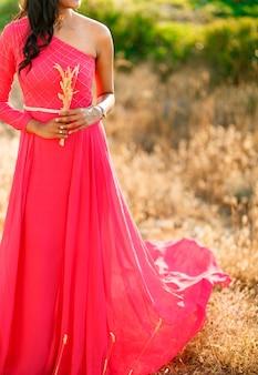 Женщина в стильном ярко-розовом платье с длинной юбкой стоит среди колосков и держит колоски.