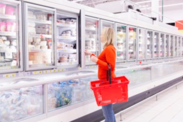 Женщина в супермаркете в отделе замороженных продуктов выбирает продукт.