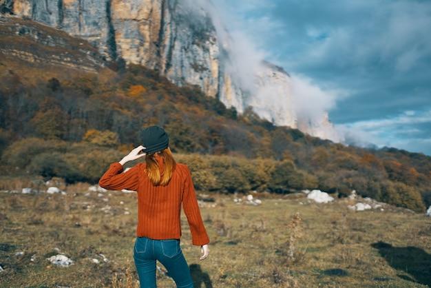 セーターを着た女性が両手を頭の後ろに持って、高山の風景青い空の雲を見ています