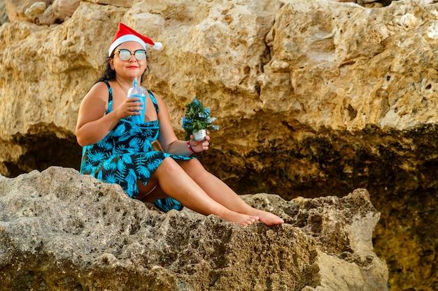 Женщина в купальнике и шляпе санта-клауса на скалистом берегу моря