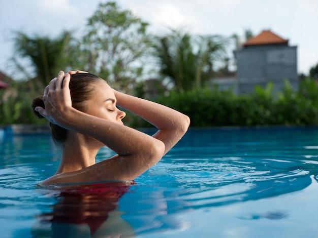 透明なプールの水で水着を着た女性が頭の後ろで手を握る