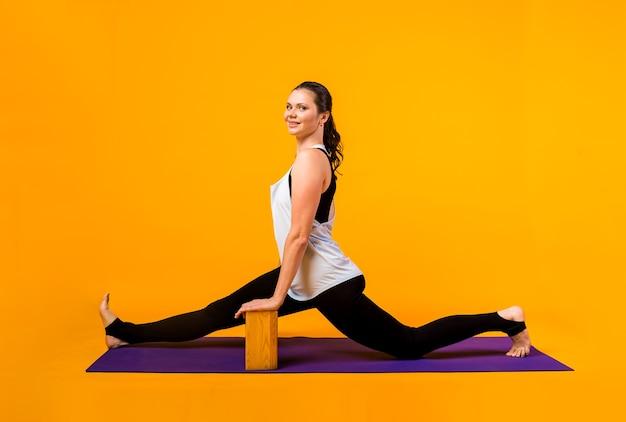 トラックスーツを着た女性がオレンジ色の壁にある紫色のマットの上でレンガを使ってヨガの練習をします