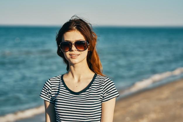 Женщина в футболке и очках гуляет по песчаному берегу на пляже у синего моря