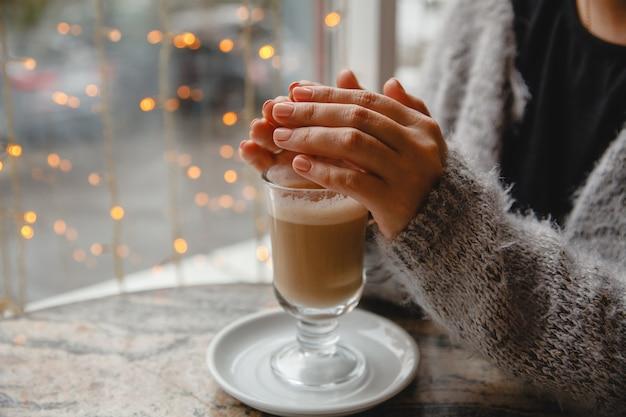 Женщина в теплой куртке сидит за столиком у окна и греет руки кофе.