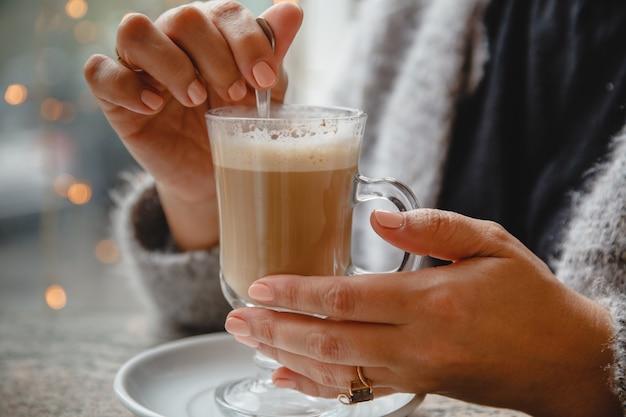 Женщина в теплой куртке сидит в кафе за столиком у окна и помешивает кофе. только руки в кадре