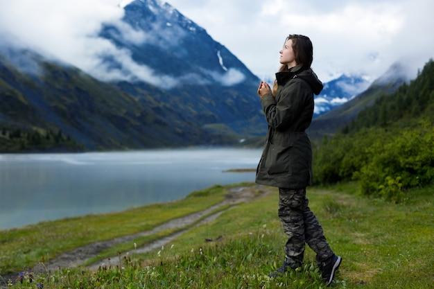 長い髪の暖かいジャケットを着た女性は、寒い湿気の多い天気の霧の中で山を背景に立っています