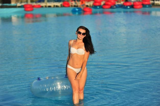ウォーターパークで膨脹可能な円を持つ白い水着の女性