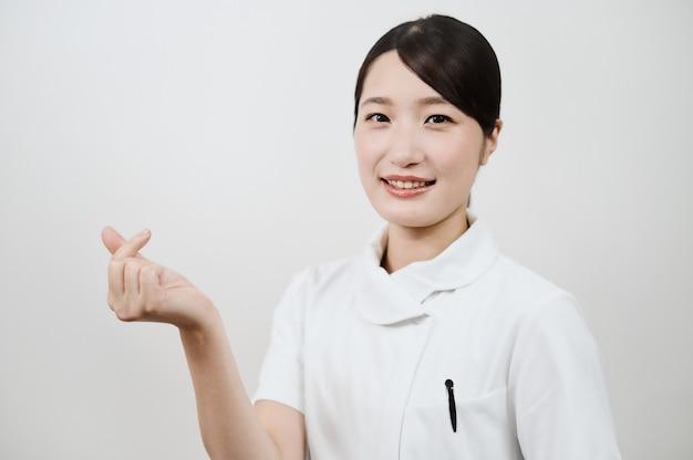 Женщина в белом халате делает след пальцами в сердце