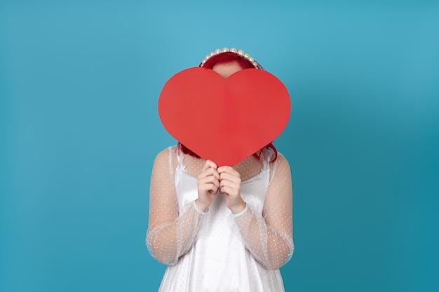 Женщина в белом платье и с рыжими волосами прячет лицо за большим бумажным красным сердцем