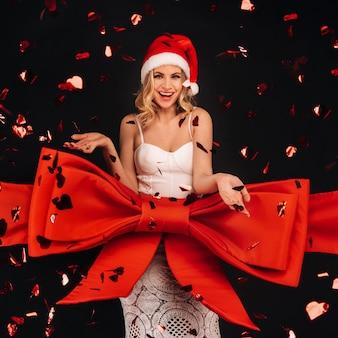 黒の背景に贈り物として白いドレスを着た女性は、空飛ぶ紙吹雪でお祝いのリボンに包まれています。