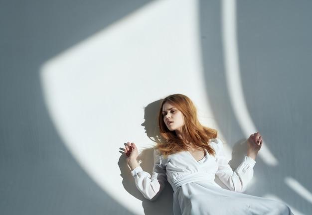 白いドレスを着た女性は、魅力的なポーズの明るい背景に横たわっています