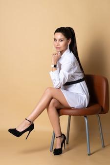 흰 드레스를 입은 여자가 노란색 벽에 의자에 앉는다.