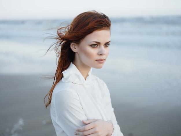 白いドレスを着た女性が海岸の自由の贅沢に沿って歩く