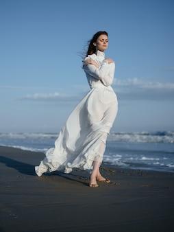 白いドレスを着た女性が海の岸にある濡れた砂の上を歩く