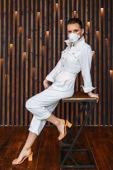 Женщина в белом комбинезоне с противовирусной маской на лице. модель сидя на стуле