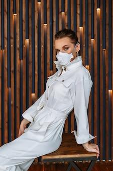 顔に抗ウイルスマスクが付いた白いジャンプスーツのドレスを着た女性。椅子に座っているモデル