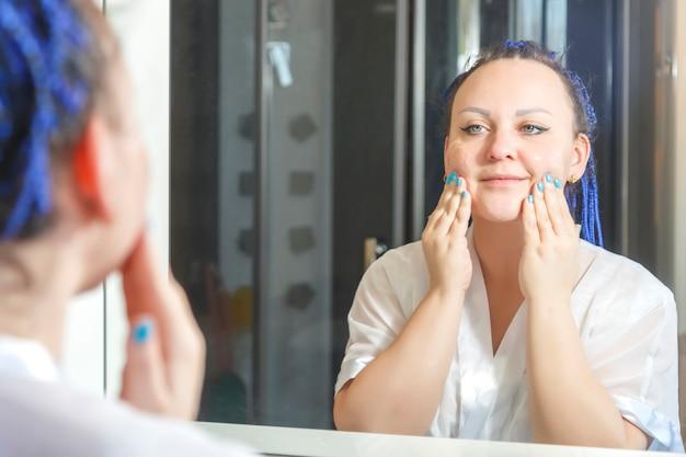 거울에 욕실에서 파란색 아프로 헤어 스타일로 흰 가운을 입은 여성이 얼굴에 스크럽을합니다.