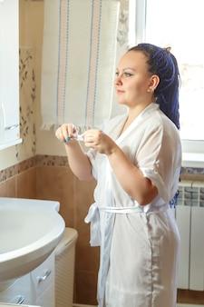 Женщина в белом халате с голубой прической афро в ванной у зеркала с умывальником с зубной щеткой в руках