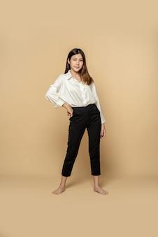 白いシャツと黒いズボンを着た女性が両手を腰に当てて立っている