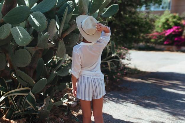 흰 셔츠와 모자를 입은 여자가 선인장 옆에 서있다.