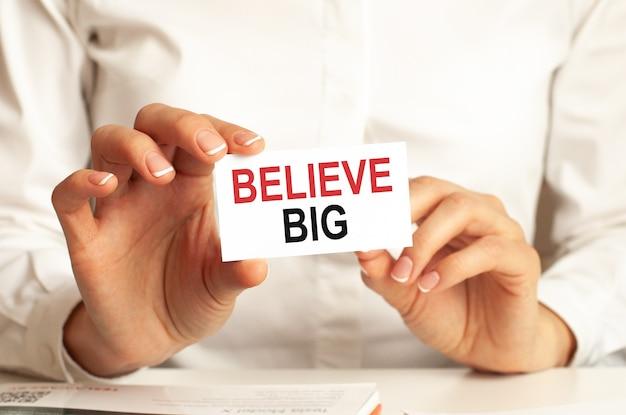 흰 셔츠를 입은 여성이 believe big라는 텍스트가있는 종이를 들고 있습니다. 회사를위한 비즈니스 개념.