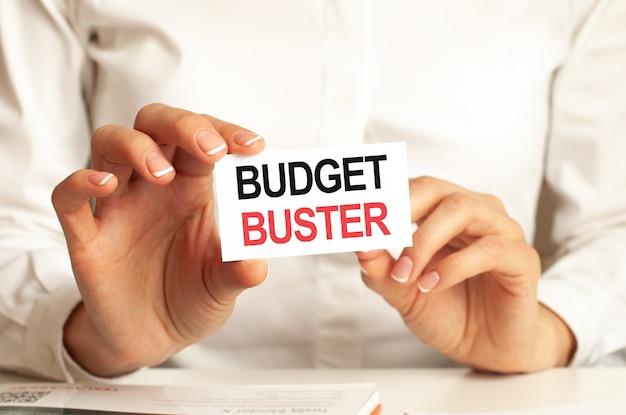 白いシャツを着た女性が、「budgetbuster」というテキストの入った紙を持っています。企業のためのビジネスコンセプト。