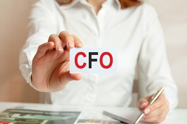 흰 셔츠를 입은 여성이 cfo라는 텍스트가있는 종이를 들고 있습니다. 회사를위한 비즈니스 개념. cfo-최고 재무 책임자 (cfo)의 약자.