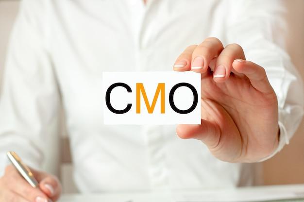 흰 셔츠를 입은 여성이 cmo라는 텍스트가있는 종이를 들고 있습니다. 회사를위한 비즈니스 개념. cmo-최고 마케팅 책임자의 약자.