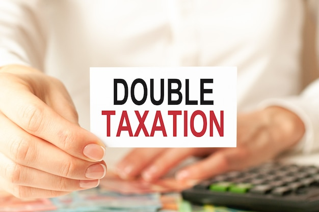 Женщина в белой рубашке держит листок бумаги с текстом: двойное налогообложение, бизнес-концепция.