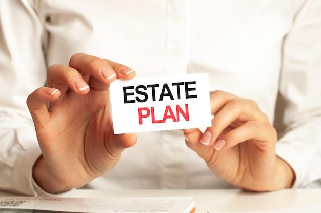 흰 셔츠를 입은 여성이 estate plan이라는 텍스트가있는 종이를 들고 있습니다. 회사를위한 비즈니스 개념.