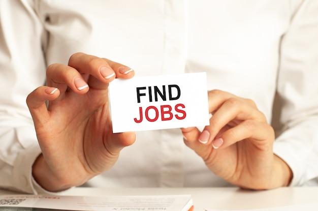 白いシャツを着た女性が、「仕事を探す」というテキストが書かれた紙を持っています。企業のためのビジネスコンセプト。