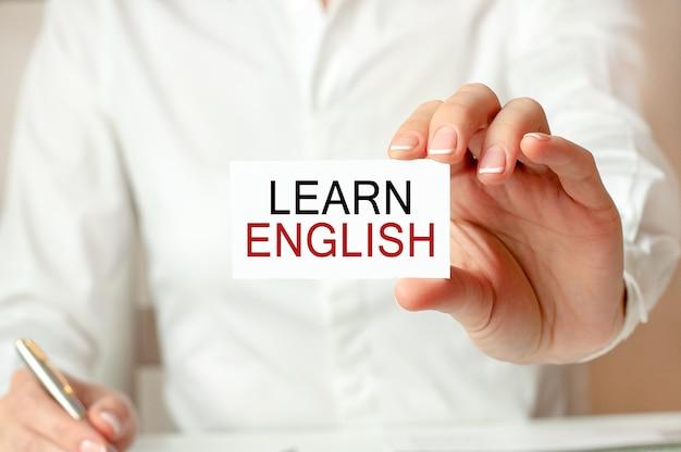 白いシャツを着た女性が、英語を学ぶというテキストの入った紙を持っています。企業のためのビジネスコンセプト