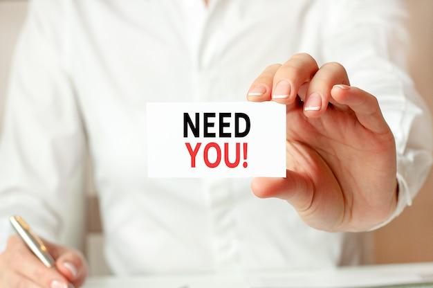 흰 셔츠를 입은 한 여성이 당신이 필요합니다:라는 문구가 적힌 종이를 들고 있습니다. 회사에 대한 비즈니스 개념입니다.