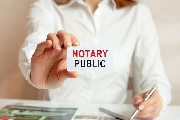 Женщина в белой рубашке держит листок с текстом: нотариус. бизнес-концепция для компаний