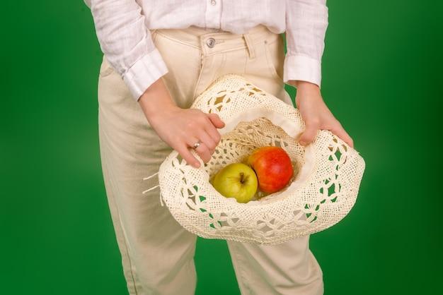 흰 셔츠를 입은 여성이 녹색 배경에 모자에 사과를 들고 있습니다. 다이어트, 건강 식품, 채식주의의 개념.