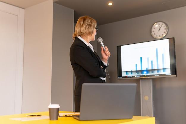 흰 셔츠를 입은 여성이 비즈니스 룸에서 청중을 코칭하고 있다