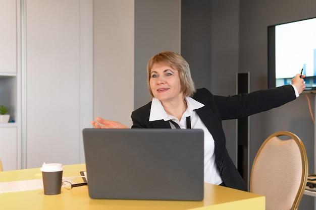 흰 셔츠를 입은 여성이 비즈니스 룸에서 청중을 코칭하고 있습니다.