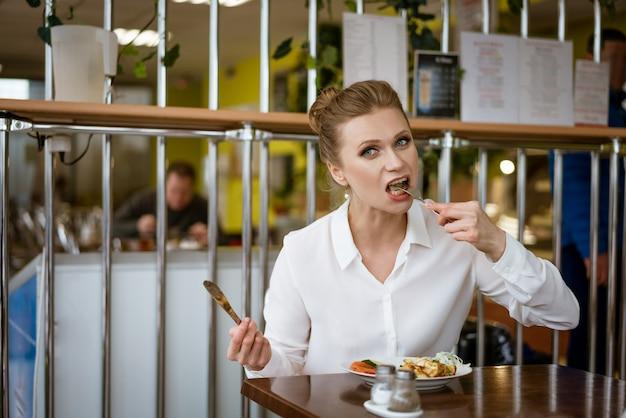 白いシャツを着た女性が手にナイフとフォークで食べるテーブルに座っています。