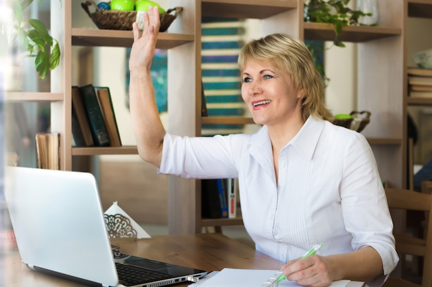 Женщина в белой рубашке работает на ноутбуке в офисе. женщина средних лет встречает вас рукой в кафе.