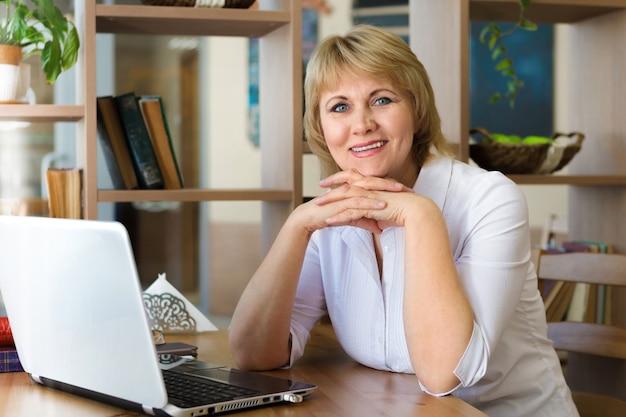 Женщина в белой рубашке работает на ноутбуке в офисе. женщина средних лет улыбается в кафе.