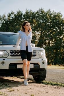 도로 위의 흰색 차 옆에 흰색 셔츠를 입은 여성. 자연으로의 여행, 도시 밖에서의 휴식. 세로 사진