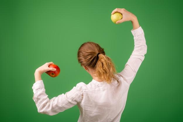 흰 셔츠를 입은 여성이 녹색 배경에 사과의 힘을 보여줍니다. 다이어트, 건강 식품, 채식주의의 개념.