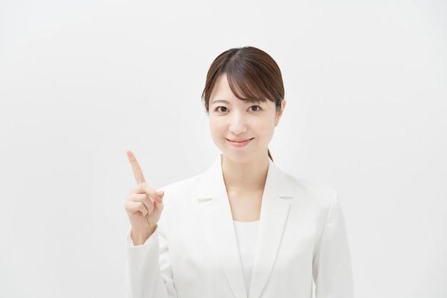 指を上げてポーズをとる白いスーツの女性
