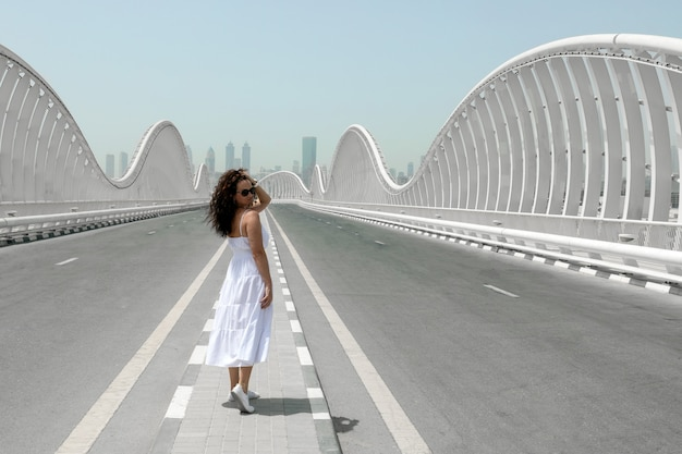 ドバイのメイダン橋、街に向かって空の道を歩いている白いサンドレスの女性