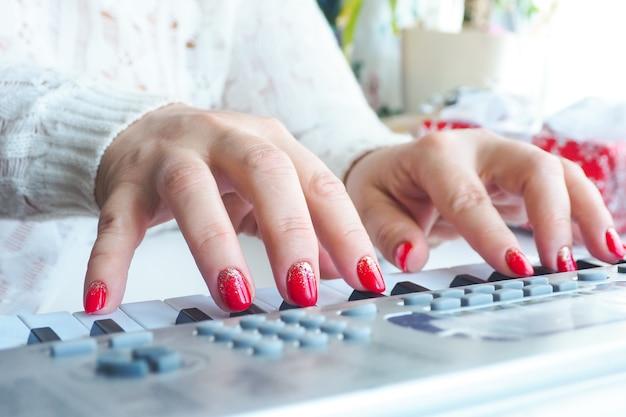 白いセーターを着て、赤い明るいマニキュアを着た女性がシンセサイザーを演奏します。