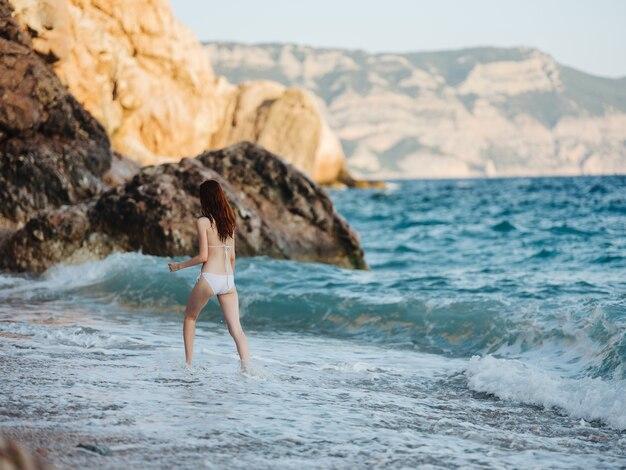 白い水着を着た女性が山の風景の新鮮な空気の海岸に沿って歩きます。高品質の写真