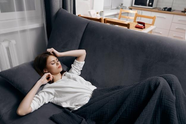Женщина в белой футболке лежит на диване под одеялом и жестикулирует руками