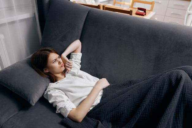 Женщина в белой футболке лежит на диване под одеялом.